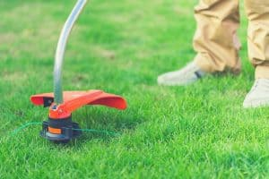 man using electric string trimmer in garden