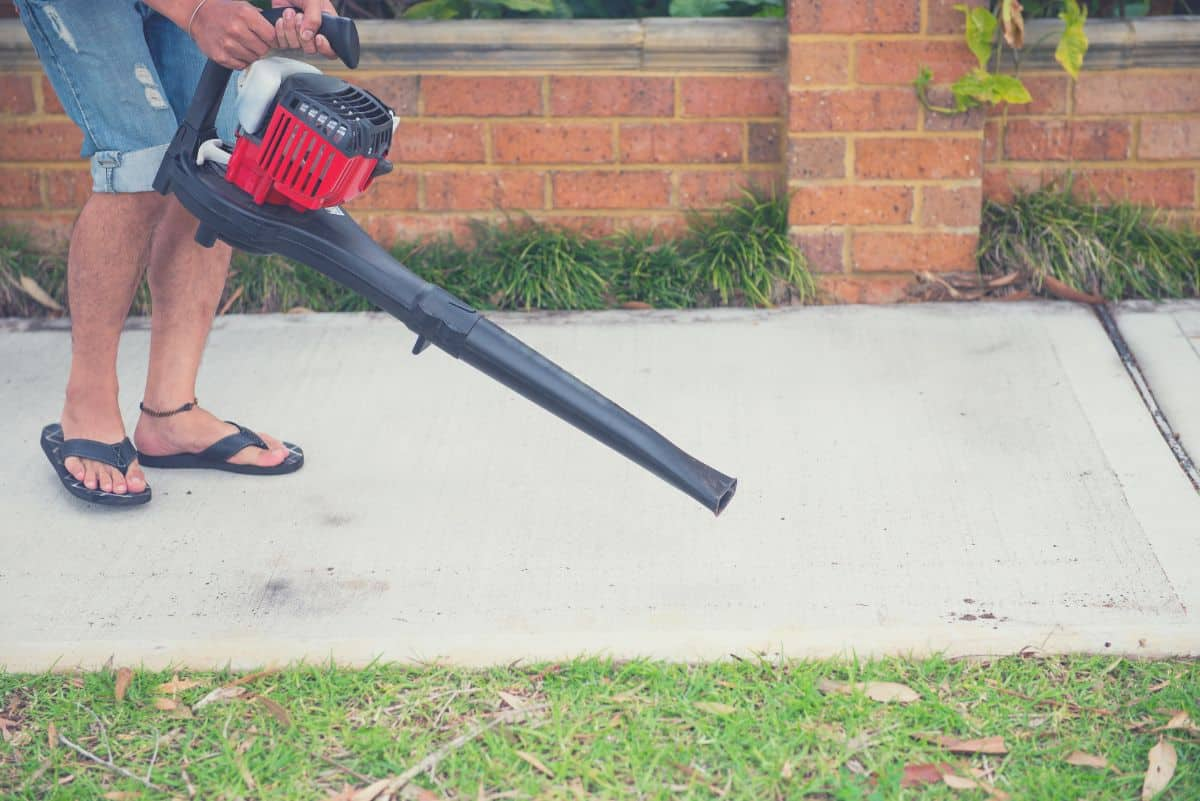 man using gas powered leaf blower in yard