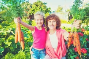 woman and daughter with carrots in the garden