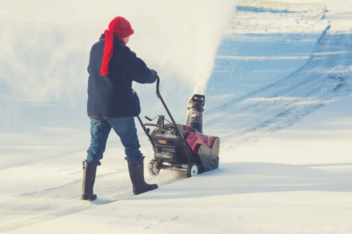 woman using cordless snow blower in yard