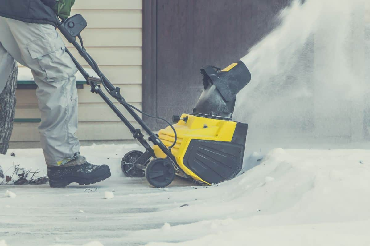 man using electric snow blower in the yard