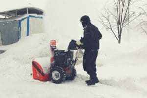 man using single stage snow blower in yard