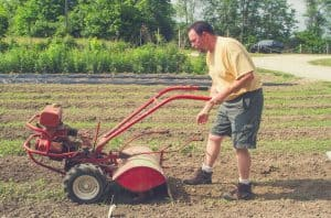 farmer tilling the garden with a rear tine tiller