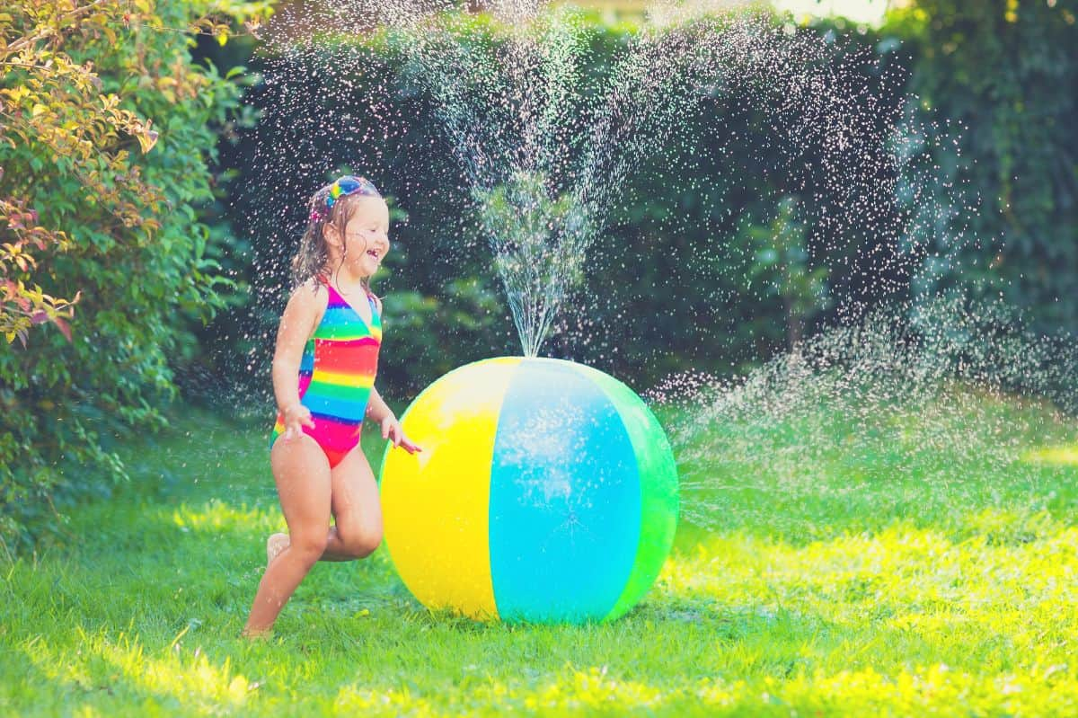 kid enjoying beach ball sprinkler
