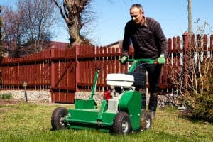 gardener using lawn aerator