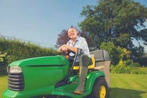 gardener on tow behind lawn sweeper